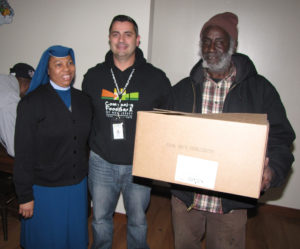 From left: Sister Mary Prisca, care coordinator, Eddie Dias of the Community FoodBank of NJ and Gardens Senior resident Howard Williams.