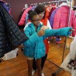 It might be July, but children were excited to try on winter coats at the Back 2 School Store.
