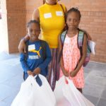 Oluremi Oluwatodimu and her children Elijah, 6, and Victoria, 8, with their shopping bags from the ninth annual Back 2 School Store. They are residents of New Community Harmony House, a transitional housing facility for homeless families in Newark.