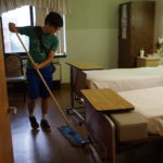 Saint Peter's Prep student Charlie Williams sweeps a room at Extended Care, New Community's nursing home.