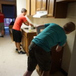 Daniel Cetera and Xavier Morales from Saint Peter's Prep clean the kitchen in a unit of Harmony House, New Community's transitional housing facility for homeless families.