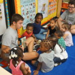 Daniel Cetera reads to a group of children at New Community Harmony House Early Learning Center.
