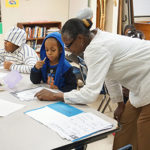 Harmony House Youth Coordinator Angela Hall helps a student with homework during the after-school program.