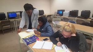 Lead Academic Enrichment Instructor Odette Phillip, standing, helps students with their work.