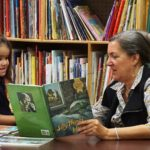Judith Robertson of the Essex Regional Educational Services Commission reads with a Harmony House student. Robertson serves as a teacher for the after-school program.