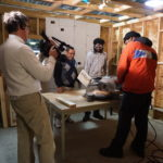 Video Life Productions Owner John Pallone captures New Community Workforce Development Center Building Trades Specialist Instructor William Robinson observing as a student uses a circular saw.