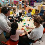 Video Life Productions Owner John Pallone films floating  teacher's aide Shanell Sing interacting with children at Community Hills Early Learning Center.