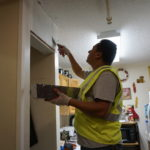A worker spackles in an apartment at Commons Senior.