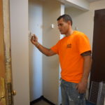 A painter at work in an apartment of Douglas Homes.