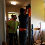 Workers affix a new door in a Gardens Senior apartment.