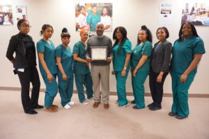 New Community Workforce Development Center Director Rodney Brutton holds the certificate of accreditation awarded to the school by the Commission of the Council on Occupational Education. He's surrounded by students and staff members.