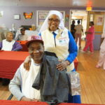 Sister Elizabeth Lima, chaplain at Extended Care, with resident Otis Williams and clothing he received.