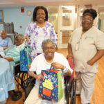 Extended Care resident Sara Dansby excitedly takes a gift during Adopt-A-Resident Day. Unit Manager Eka Ehize, left, and Activity Aid Linda Murphy pose with her.