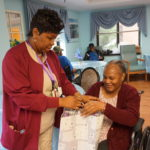 Extended Care Assistant Director of Activities Yonette Semple gives resident Dorothy Mair a present during Adopt-A-Resident Day.