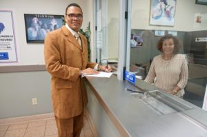 Rev. Dr. Miles S. Callender, AAS, BSW, CSW, MSW, Ph.D., at the window of New Community Federal Credit Union with NCFCU Director Mulu Gebreyesus.