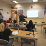 An education development executive from Apple speaks with Academic Enrichment students about coding May 9 as New Community Workforce Development Center Director Rodney Brutton looks on.