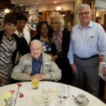 New Community Founder Monsignor William J. Linder, seated, celebrated his 82nd birthday June 5, 2018 with several NCC staff members. Extended Care Administrator and Director of Health and Social Services Veronica Onwunaka, Chief of Staff Kathy Spivey, CFO Elizabeth Mbakaya, Board Member and Outreach Coordinator Madge Wilson and CEO Richard Rohrman, standing left to right, accompanied Monsignor Linder to a restaurant for lunch. Photo courtesy of Veronica Onwunaka.