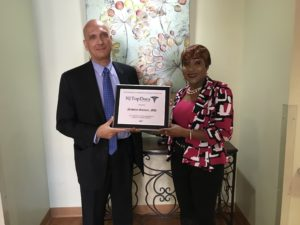 Dr. Nicholas Guittari, Extended Care medical director, and Veronica Onwunaka, administrator at Extended Care and director of Health and Social Services for New Community, show off the plaque designating Guittari as a Top Doctor for 2017.