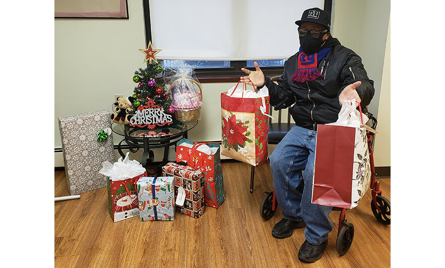 Manor Senior Christmas Presents Man Holding 2 Bags for Website