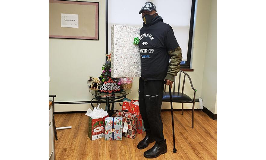 Manor Senior Christmas Presents Man Holding Snowflake Gift for Website