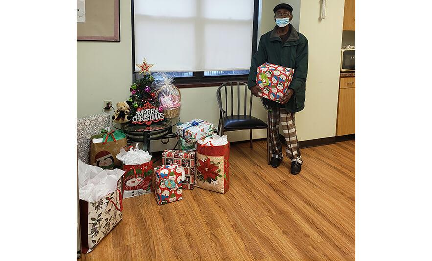 Manor Senior Christmas Presents Man Holding Snowman Gift for Website